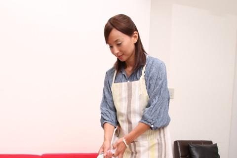 床に掃除機をかける女性