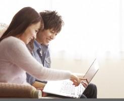 パソコンを見ながら楽しそうなカップル