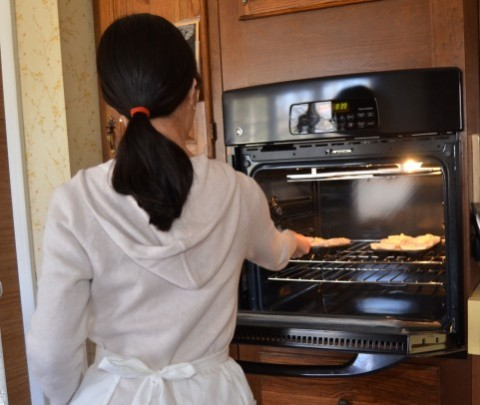 オーブンで調理する女性